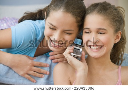 Hispanic sisters using same cell phone - stock photo