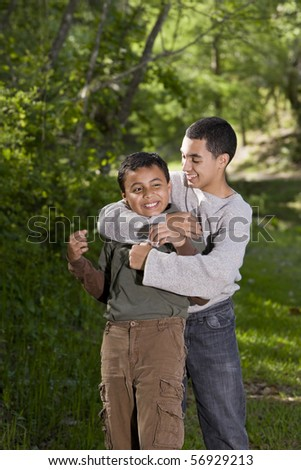 Hispanic teenage boy playing with and teasing brother - stock photo