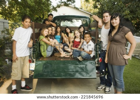 Hispanic teenagers and young adults in back of truck - stock photo