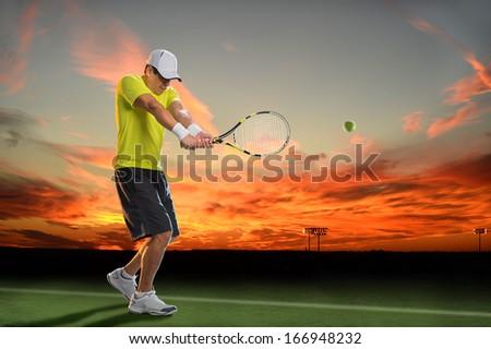 Hispanic tennis player hitting ball during sunset - stock photo