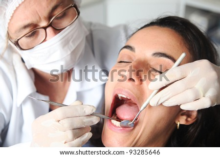 Hispanic woman at the dentist with the mouth wide open - stock photo