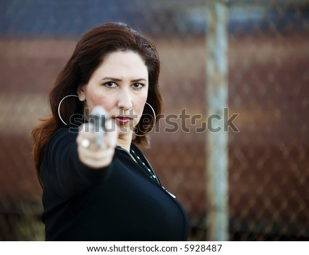 Hispanic woman behind a wall holding a handgun in ready to fire position. - stock photo