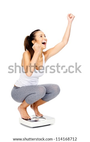 Hispanic woman celebrating and cheering a weightloss goal achievement isolated on white and on a scale - stock photo
