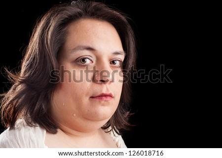 hispanic woman crying on a black background - stock photo