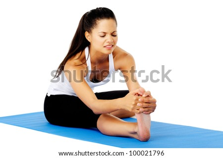 Hispanic woman feeling pain while doing the head to knee yoga pose. This is part of a series of various yoga poses by this model, isolated on white - stock photo