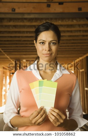 Hispanic woman holding paint swatches at construction site - stock photo