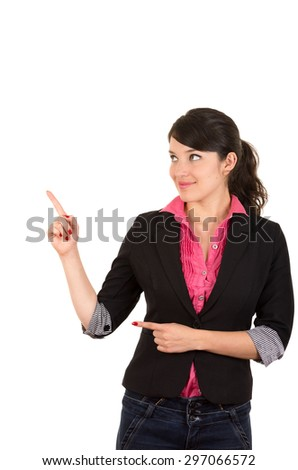 Hispanic woman in pink shirt and black blazer jacket pointing right hand upwards while left arm finger points same direction from hip - stock photo