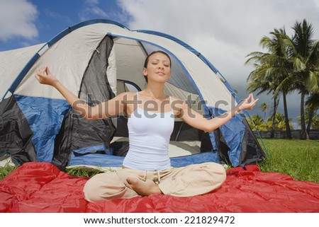 Hispanic woman meditating in front of tent - stock photo