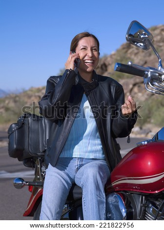 Hispanic woman on motorcycle talking on cell phone - stock photo