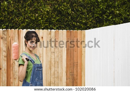 Hispanic woman painting fence - stock photo