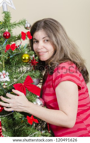 Hispanic woman putting together the traditional Christmas tree