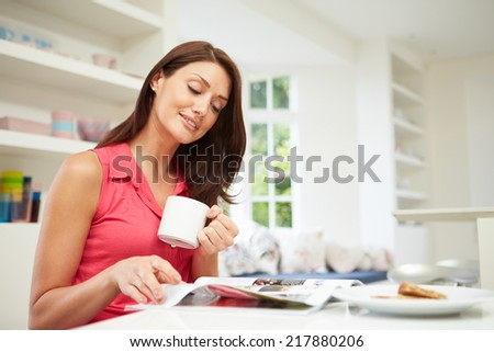 Hispanic Woman Reading Magazine In Kitchen At Home - stock photo