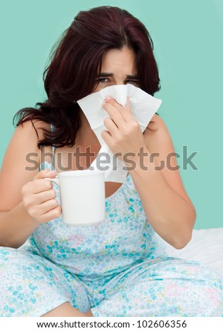 Hispanic woman sick with the flu with a white paper tissue in her hand and holding a cup of tea