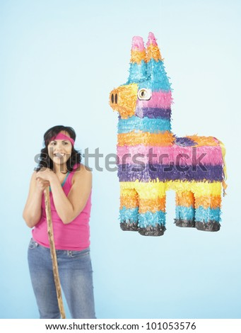 Hispanic woman standing next to pinata - stock photo