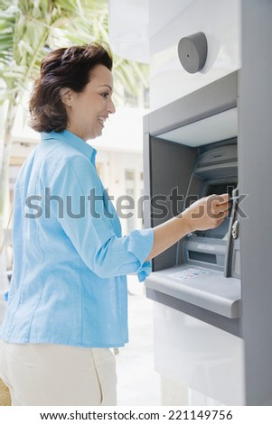 Hispanic woman using automatic teller machine