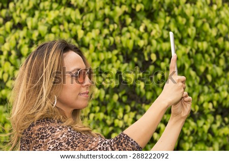 Hispanic woman with tablet outdoors wearing sunglasses posing for selfie - stock photo