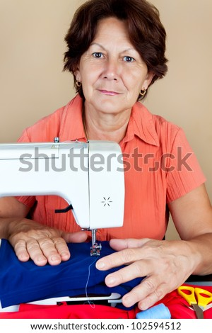 Hispanic woman working on a sewing machine and looking at the camera - stock photo