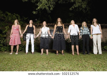 Hispanic women holding hands in a row - stock photo