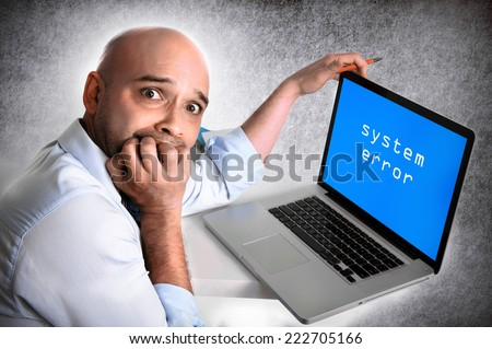 hispanic worried and anxious businessman at work biting finger nails in stress working on laptop computer in system error operative system crash in edgy studio lighting and background - stock photo