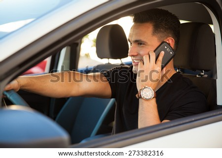 Hispanic young man talking on his phone and driving a car - stock photo
