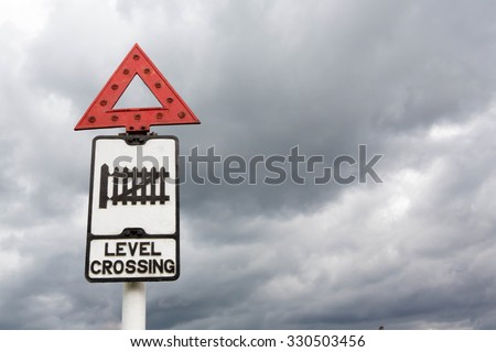 Historic British Road Sign indicating a Railway Level Crossing ahead against a cloudy sky background.
