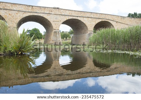 Historic building in heritage listed Richmond, Tasmania, oldest convict built stone bridge in Australia, with mirror image in water of river underneath arches, tourist attraction close to Hobart. - stock photo