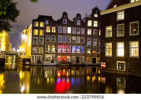 Historic buildings of old Amsterdam and canal at night. - stock photo