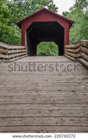 Historic Burr arch covered bridge over Sugar Creek in Illinois - stock photo