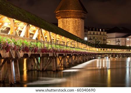 Historic Chapel bridge spanning a river (Reuss) in Lucerne Switzerland - stock photo