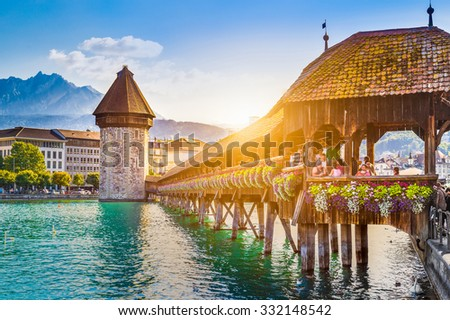 Historic city center of Lucerne with famous Chapel Bridge and Mount Pilatus summit in the background in golden evening light at sunset with blue sky and clouds, Canton of Lucerne, Switzerland - stock photo