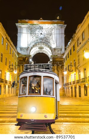 historic classic yellow tram of Lisbon built partially of wood in front of triumphal arch ?Arco Monumental? at night at the beginning of commerce square, Portugal - stock photo