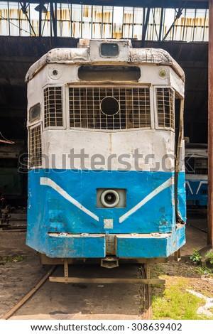Historic electric tram of Kolkata standing at a depot. - stock photo