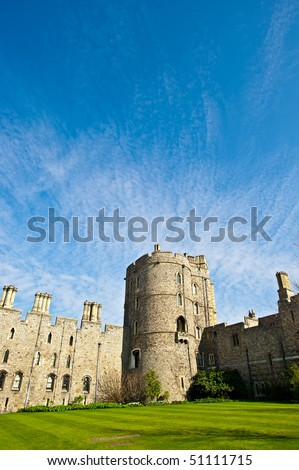 Historic English castle with blue sky and green lawn. This is Windsor Castle, the oldest and largest occupied castle in the world and home to Queen Elizabeth II. - stock photo