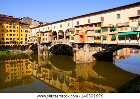 Historic Ponte Vecchio with reflections in the Arno, Florence, Italy - stock photo
