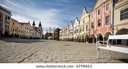 Historic square, Telc City, Czech Republic - bench on stone paved square, unique buildings, blue sky - stock photo