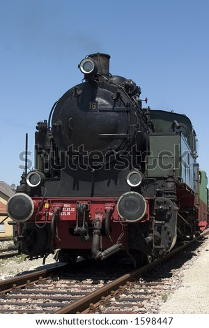 Historic steam train on tracks in a station