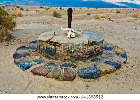 Historic Stovepipe Well and skull, Death Valley National Park, California - stock photo