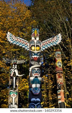 Historic totem poles, created by First Nations people, in Stanley Park, Vancouver, Canada.  Colorful Autumn foliage in the background. - stock photo