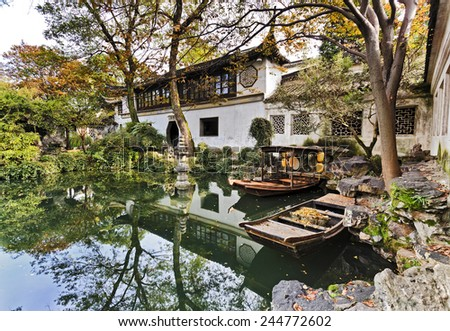 Historic traditional botanic garden in Chinese city Suzhou interior view of architecture around still pond with boats and trees - stock photo