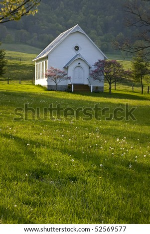Historic white clapboard country church nestles on a hillside in the Virginia mountains.