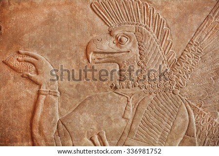 Historical Assyrian relief of bird face genie carrying a cedar-cone, made for Palace at Nimrud in 850BC. Exhibition of artifacts in Pergamon Museum, Berlin.  - stock photo