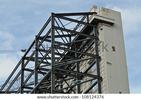 Historical building facade support corner of the building, part of old wall crane wires and blue sky in background - stock photo