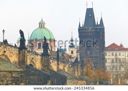 Historical buildings and Charles bridge across Vltava river in cloudy autumn day, Prague, Czech Republic - stock photo