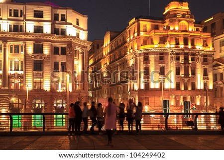 historical buildings in shanghai bund at night with tourists - stock photo