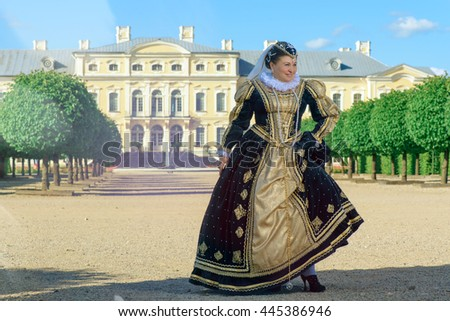 Historical cosplay. Beautiful woman in the similitude of Marguerite of Navarre, queen of France ancient dress in the garden near palace - stock photo