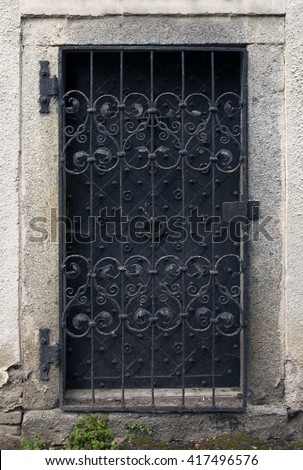 Historical house door. Big metallic old door. One timber leaf, closed black gateway with metal and nails. Exterior country situation. Rural entry architecture element. Village foundation background.