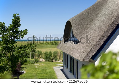 historical house with thatched roof and blue sky at the German Baltic Sea coast, Germany, Europe,  ein typisches Haus mit Reetdach an der deutschen Ostseekueste, Deutschland, Europa - stock photo