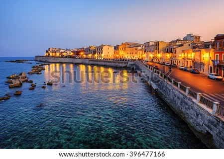 Historical houses facing Mediterranean sea on the island Ortigia, the oldes part of Syracuse town, Sicily, Italy, on late evening - stock photo
