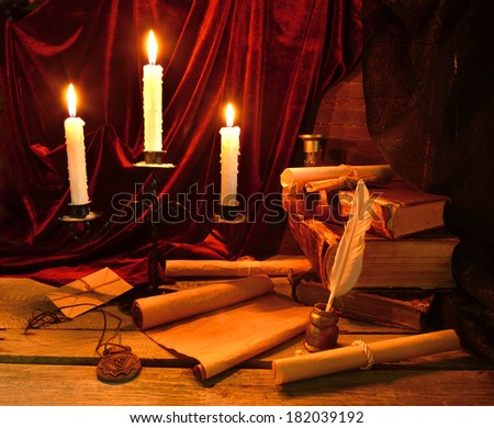 Historical still life with old books, written implements and burning candles in candlelight - stock photo