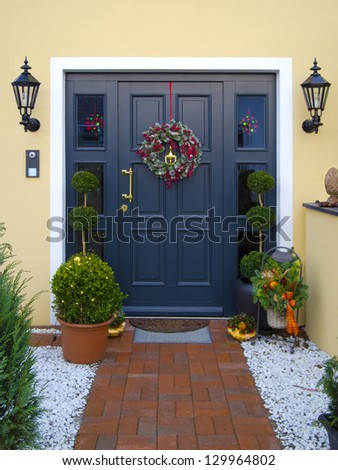 historical wooden front door decorated with garland - stock photo
